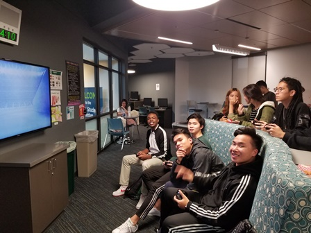 Students smiling playing video games